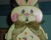 Wooden Bunny Baket painted with a Chalky Finish Paint that is Spring Green, Daisies, Ladybugs and Butterflies, a bag of rag eggs is included