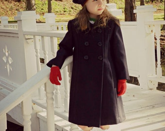 Girls Navy blue wool winters coat.  It has two pockets and six fastening buttons down the front. Sizes  from 2 through 8 years  17309