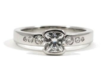 Platinum and Forever Brilliant Cushion Cut Moissanite Half Bezel Engagement Ring with Gradating Moissanites