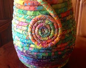 Fabric coiled pot with spiral in multi-colored batiks.