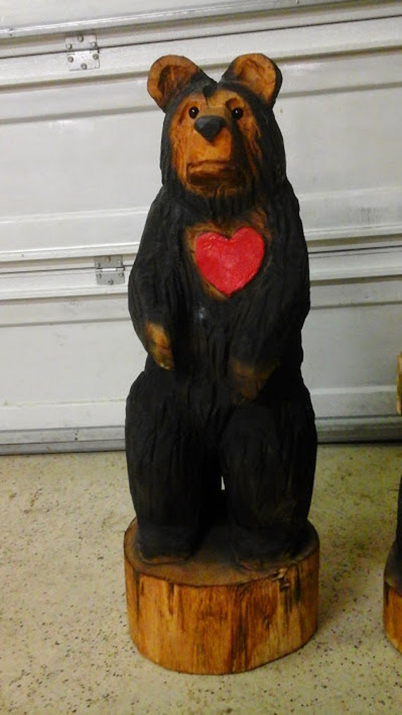 Chainsaw carved black bear with a red by carvnstitch