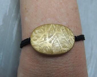 Bracelet adorned black macrame of a golden Pebble