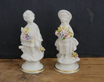 Pair of  vintage Capodimonte figurines in bisque porcelain by Marcolin. Excellent condition. Girl and boy holding flowers.