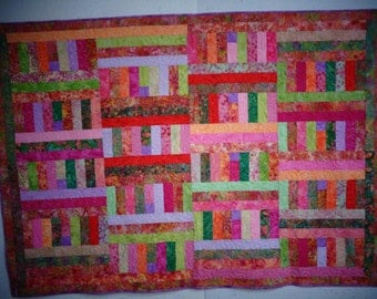 """Batiks - pinks, greens, oranges and lavenders.  54"""" x 77"""".  Longarm quilted."""