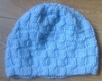 Pale blue textured hand knitted beanie hat.
