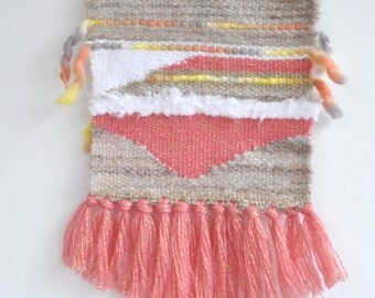 Weaving, beige, pink and white wall hanging on branch. Interior decoration.