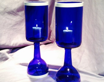 Glass hurricane candle holders from wine bottles. Pair of two sapphire blue with white detail.