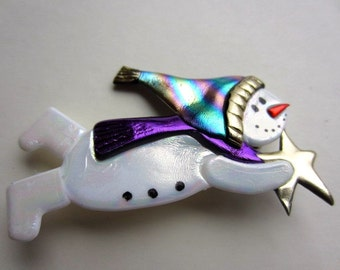 Flying Snowman with multi colored stocking cap and purple scarf holding a star pin brooch
