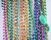Multiple strands Mardi Gras beads / plastic beads / gold blue orange purple green pink / stars dice Rio casino / gambling / party / fun