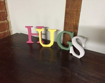 Three standing letters spelling HUGS