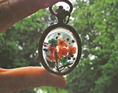 genuine flowers preserved in clear casting resin enclosed in a Vintage Oval Bronze bezel setting.