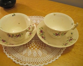 Pair of Art Deco cups and saucers, hand painted with flowers and leaves for cabinet display