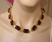 13 prong set links of rectangle dark amber   glass surrounded by gold tone prong set necklace.  Lovely vintage necklace.