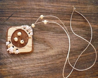 Pendant made of birch bark and wood beads on waxed thread