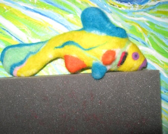 """It's a fish! It is pose able, soft, friendly and colorful.  Neede felted. 9"""" long, 3"""" wide, 4"""" from top to bottom."""