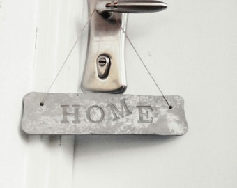 A hanging HOME sign made of concrete