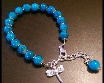 Blue mottle effect beaded bracelet with silver plated dragon fly charm.