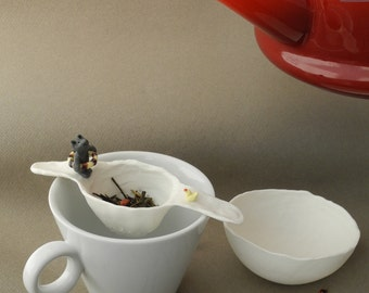 tea strainer in white porcelain with black cat and a duckling
