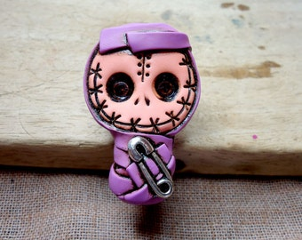 Sewn mouth baby mummy bandaged in purple with a safety pin. Mini size. Brooch or magnet (choose)