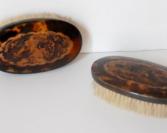 pair of brushes in tortoise shell with asian decoration