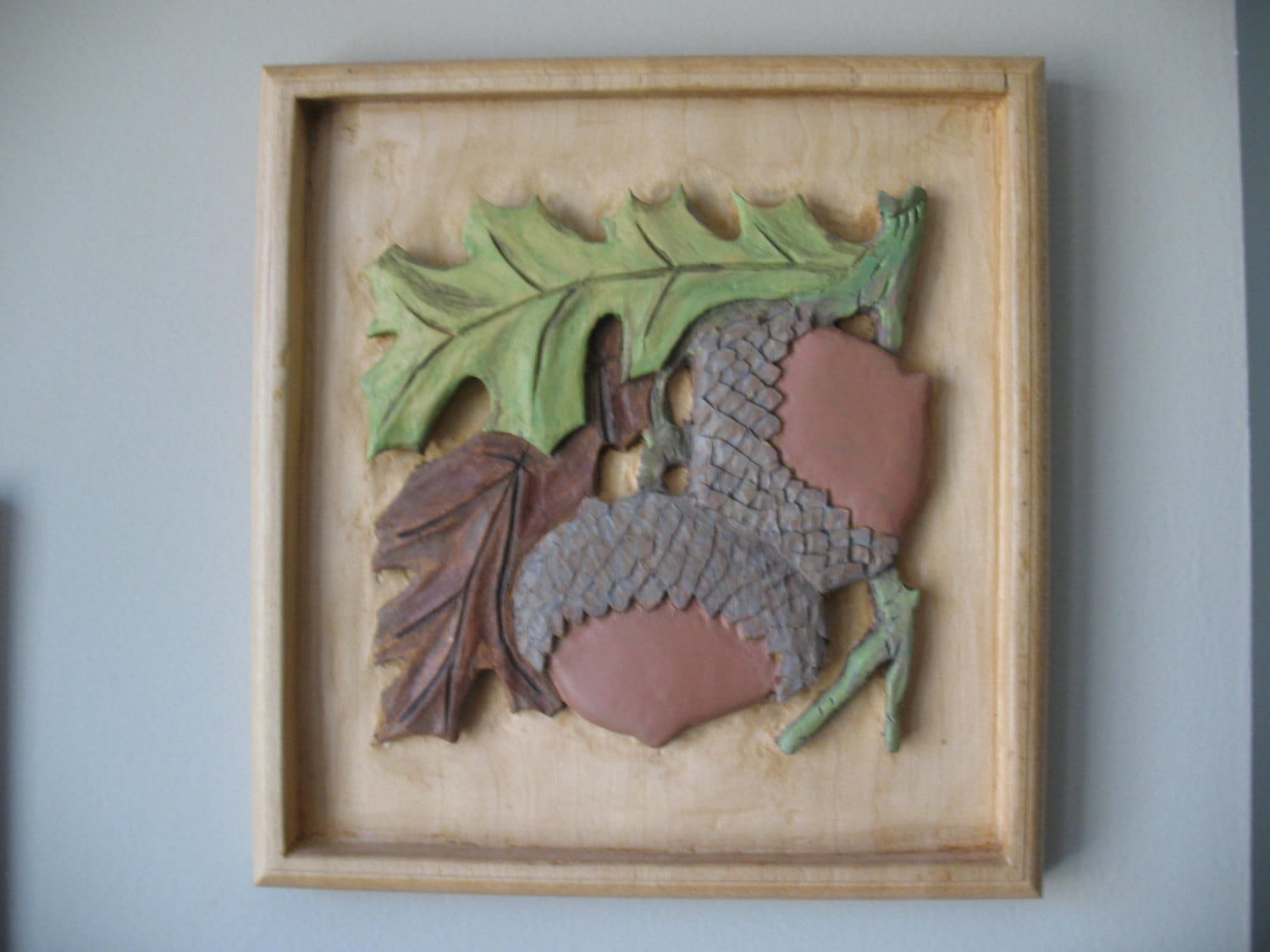 Relief carving of an oak leaf and acorn cluster