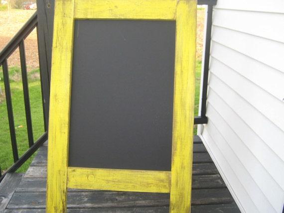 Rustic sidewalk chalkboard.  Weathered, distressed sun yellow sandwich chalkboard.  A frame, easel, wedding outdoor.