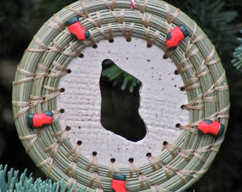 Cute hand-stitched and coiled pine needle Christmas ornament with Christmas stocking beads and Christmas stocking cutout ceramic center.