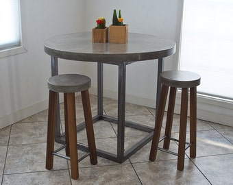 Hand-crafted concrete table top with welded steel legs.