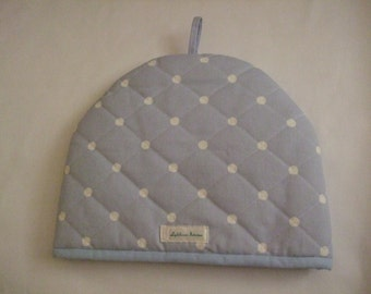 A stylish quilted padded tea cosy in organic cotton in sky blue 'dotty' design.