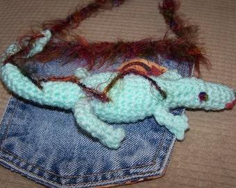 Crocheted gecko in a pocket