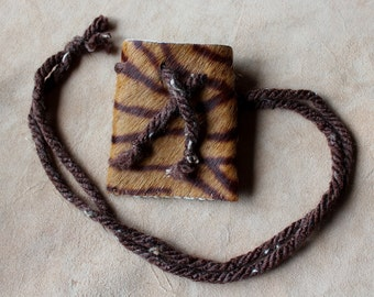Tiger-printed cow hide necklace pouch with brown yarn cords for crystals, herbs, medicine, more