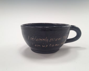 Large mouthed black and blue coffee cup with quote