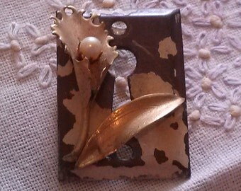 Brass keyhole with a vintage brooche