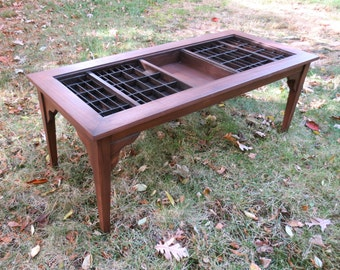 Wood coffee table in the Arts and Crafts style with a top for displaying collectibles in a built in and altered printer's type drawer.