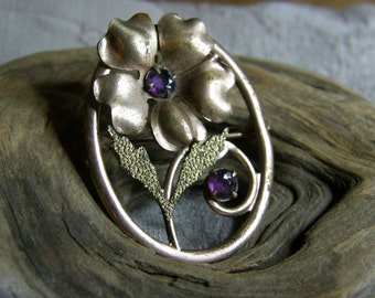 Vintage flower brooch circa the 1960's in rose and yellow gold tone metal and amethyst glass stones