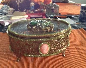 Gold filigree trinket box trimmed in green jewels