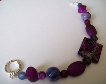 Orchid bracelet and earrings with mixed purple glass , clay and resin beads