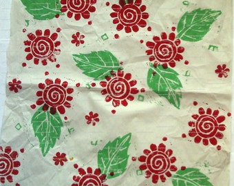 Sheet of white tissue paper, handprinted with red flower/green leaf design