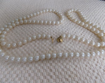 Vintage necklace, 36 inch strand 8 mm.faux pearls with embedded fold over closure in golden ball,not individually knotted