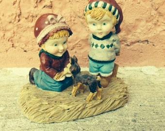 2 kids and dog figurine
