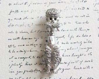 Monet poodle brooch pin with glass eyes. Maker marked Monet. Vintage silver tone poodle pin.