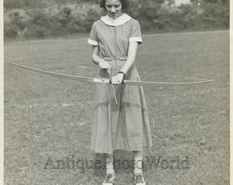 Young woman archer with bow and arrows antique photo