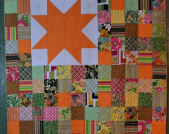 Quilted wall hanging or lap quilt. Machine pieced and quilted orange, green, white, yellow, pinks with lots of free motion quilting