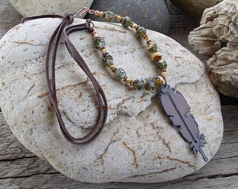 Rusted iron feather pendant hangs from glass and leather necklace