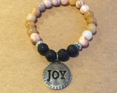 Joy Bracelet made with Peach, tan and cream beads accented with black lava beads, silver spacers and a silver Joy Charm.