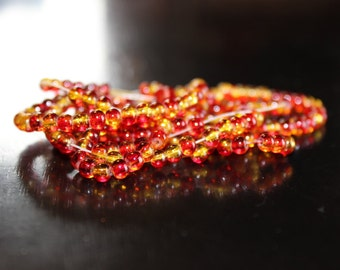 195 approx. 4 mm red and gold crackle glass beads, round and smooth