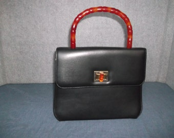 Black purse with bakelite handle, goldtone closure, inside divider with zipper pocket, black lining , no shoulder strap, synthetic purse,