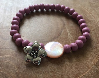 FlowerPower: an elastic beaded bracelet with pink purple wooden beads, pink mother of pearl and a metal charm in the shape of a flower