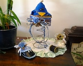 Handmade, stuffed blue bird, bird nest on lightly rusted bed spring, bed spring