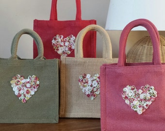 Beautiful hand finished jute lunch or gift bag with padded handles and chic decorative heart made up from pretty rose flowers.